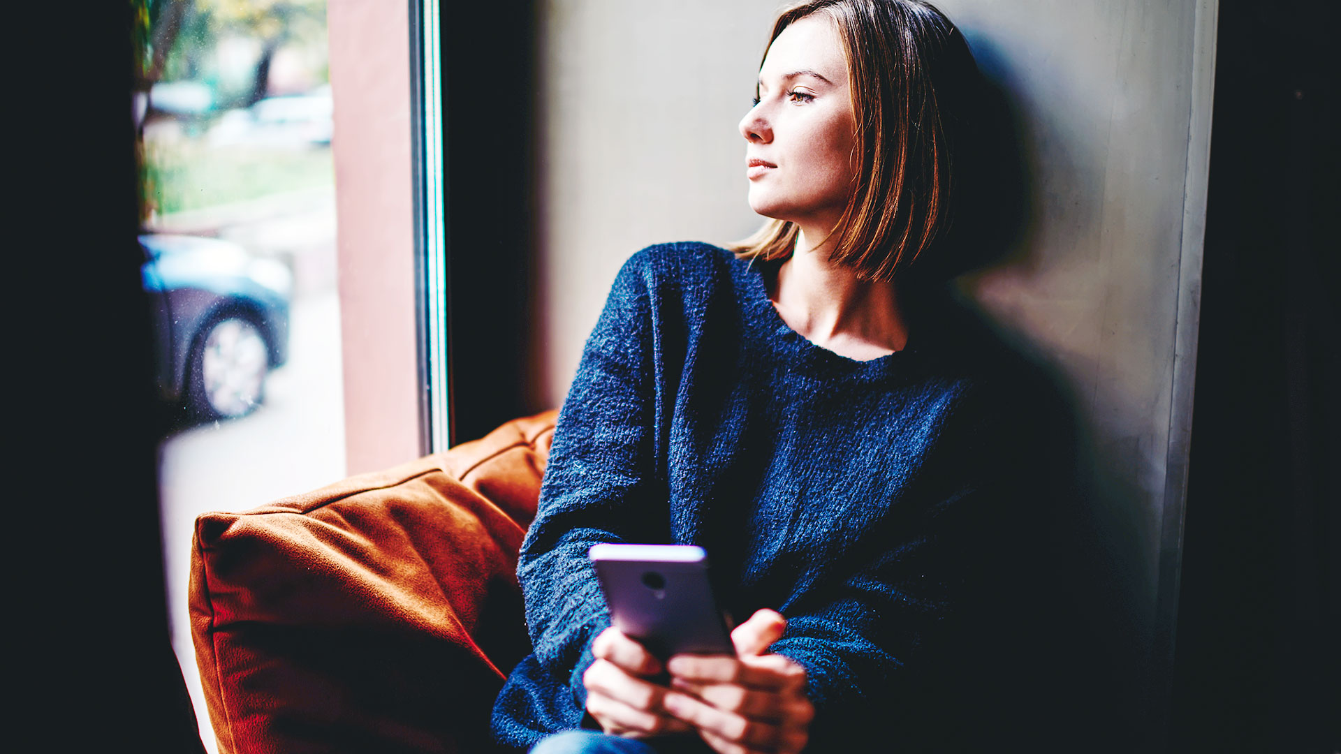 Woman looking out the window with phone in hand